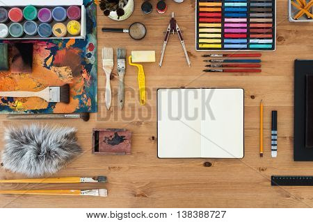 Painter workplace top view. Wooden table of an artist with art tools for drawing