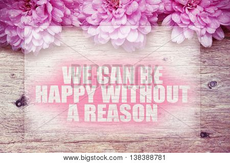 pink flowers on wooden with word We can be happy without a reason