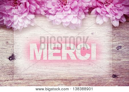 pink flowers on wooden with word Merci