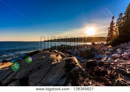 The sun goes down over the rocky coast of Main in Acadia National Pari