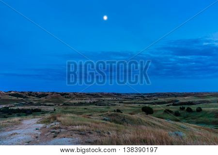 The moon is out in a blue sky in the evening at Badlands National Park