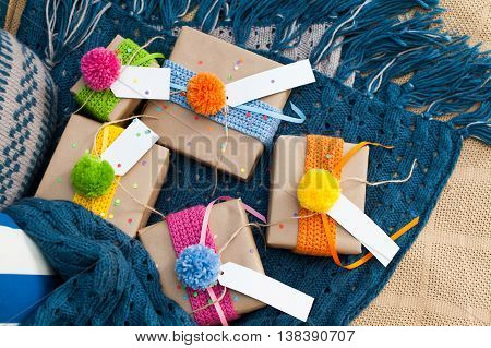Gifts wrapped in kraft paper lie on a knitted rug.