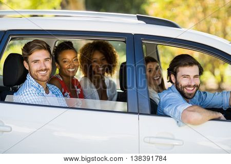 Portrait of friends looking out from car window on a sunny day