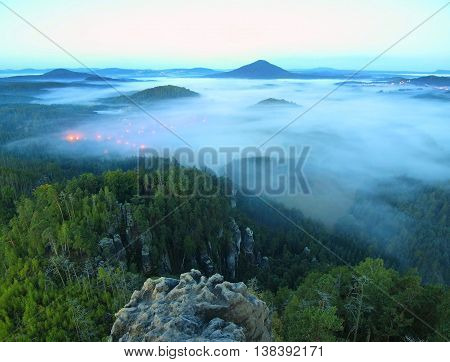 Blue misty valley after rainy night, pink orange lights are shining from village bellow. The fog is moving between hills and peaks of trees, blue sky.
