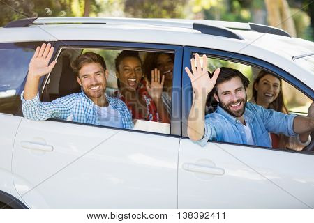Portrait of friends waving hands from car on a sunny day