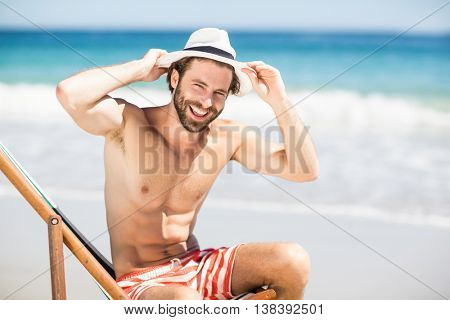 Portrait of happy man sitting on armchair at beach