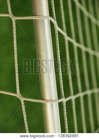 Hang bended soccer nets, soccer football net. Grass on football playground in the background