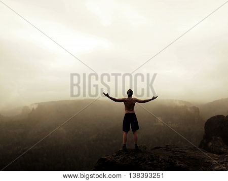 Climber in black pants. Gesture of triumph. Naked tourist on the peak of sandstone rock in national park Saxony Switzerland watching into misty landscape.