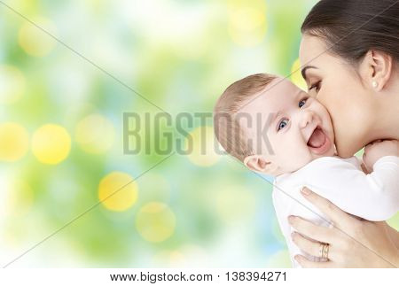 family, motherhood, parenting, people and child care concept - happy mother kissing adorable baby over green holidays lights background