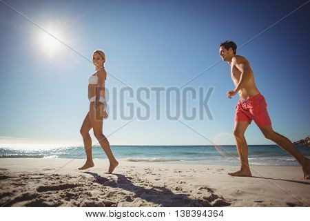Young couple running on beach in summer