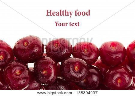 Heap of ripe cherries with water drops on a white background. Decorative frame of fruits. Isolated. Macro. Food background. Copy space.