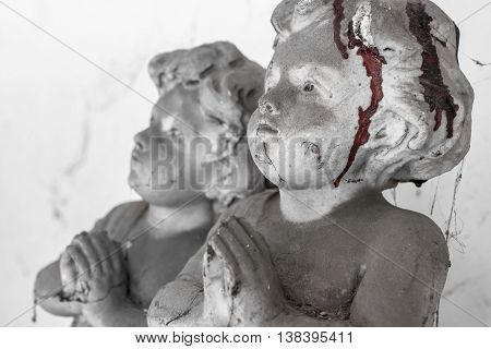 Statue of a child praying covered with cobwebs and dried blood. Defocused blurry background.