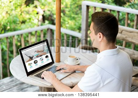 business, internet shopping, people and technology concept - close up of businessman with online shop web page on laptop computer screen on summer terrace drinking coffee