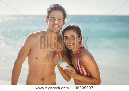 Portrait of happy young couple with sunscreen lotion on beach