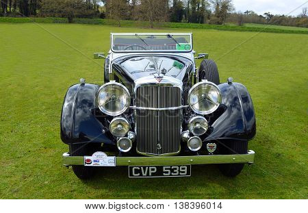 Saffron Walden, Essex, England - April 24, 2016: Classic Black Alvis motor car parked on grass.