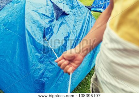 camping, travel, tourism, hike and people concept - close up of man setting up tent outdoors