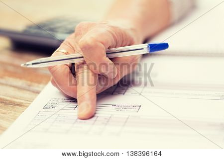 business, annuity insurance, age and people concept - close up of senior woman hand with pen checking bill