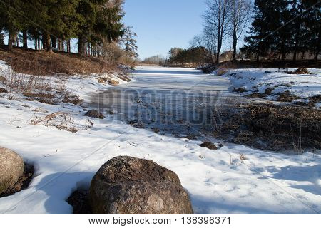 The spring creek in the snow under the sun