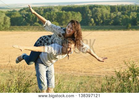 happy couple having fun on outdoor, girl riding on man back and fly - romantic travel and people concept, summer landscape with wheaten field, yellow toned