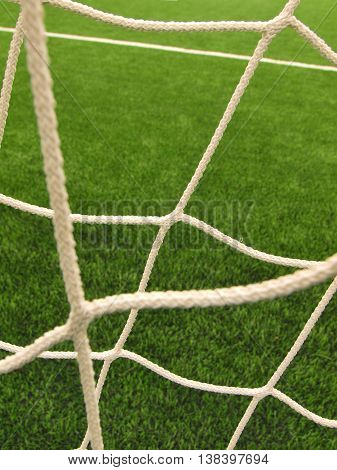 Hang bended soccer nets, soccer football net. Plastic grass and white painted line on football playground in the background