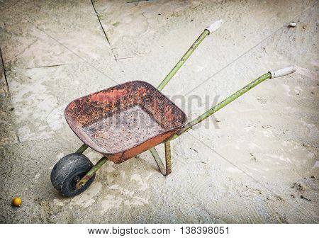Old wheelbarrow on site. Hand cart. Industrial theme.