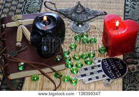 Black magic ritual with mysterious occult and esoteric symbols, objects.Black burning  skull and heart candles, magic Aladdin lamp, pendulum, runes, God hand, voodoo doll, old book with key.