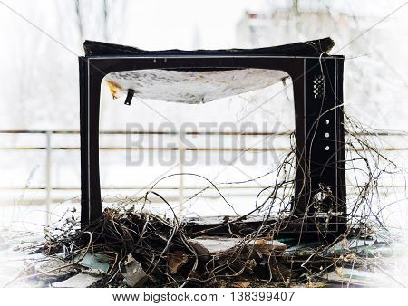 Horizontal vintage broken tvset in radioactive pripyat bokeh background