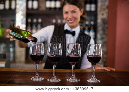 Portrait of bartender pouring a red wine in the glass at bar counter