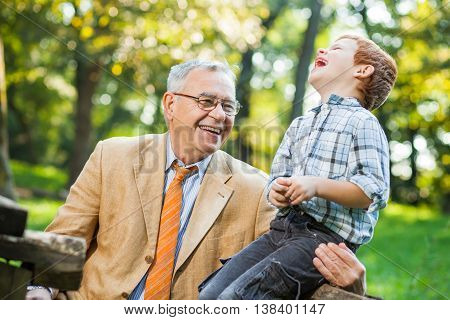 Grandfather and grandson are sitting and talking in park