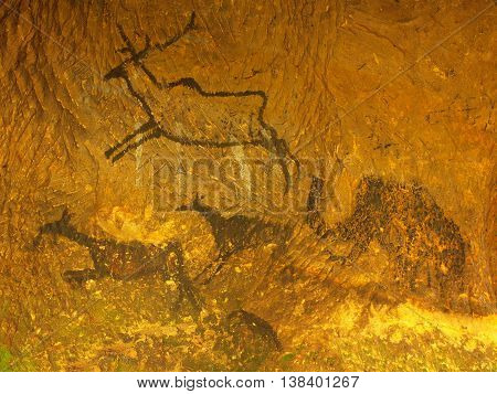 Abstract art in sandstone cave. Black carbon paint of human hunting on sandstone wall, copy of prehistoric picture. Caveman draw in cave. Mammoth draw in cave.