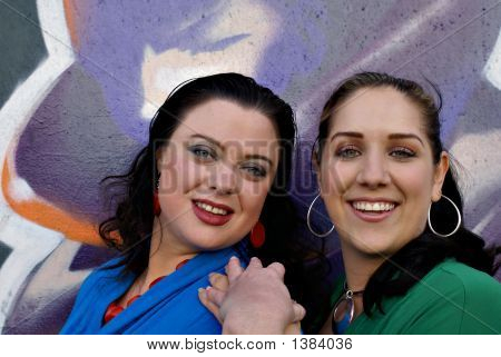 Two Young Women Against A Colorful Graffiti Background