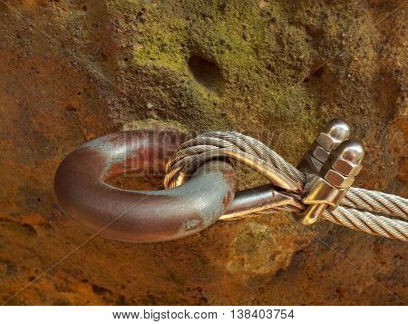 Detail of steel bolt anchor eye in sandstone rock. The end knot of steel rope. Climbers path via ferrata. Iron twisted rope fixed in block