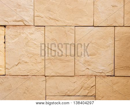 a wall from an artificial beige stone facade with rough fractured surfaces