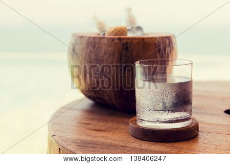 travel, tourism, drinks and refreshment concept - glass of cold water an moisturizing stuff on table at beach