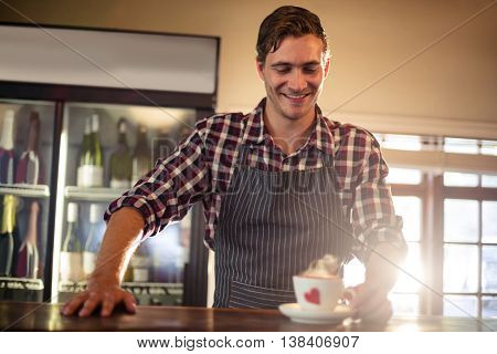 Smiling, of waiter holding a coffee cup at counter in café