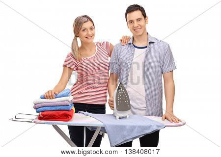 Young cheerful couple posing together behind an ironing board isolated on white background