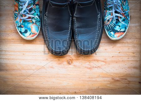 The Leather And Canvas Shoe On Wooden Background. Work Life Balance Concept