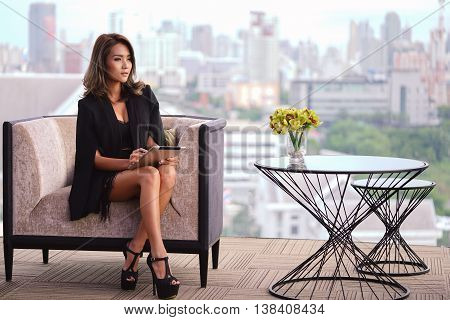 Young businesswoman sitting on the sofa and held on the tablet and looking around looks like concerned