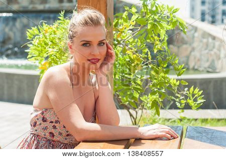 Beautiful Young Lady Sitting Outside Smiling And Posing