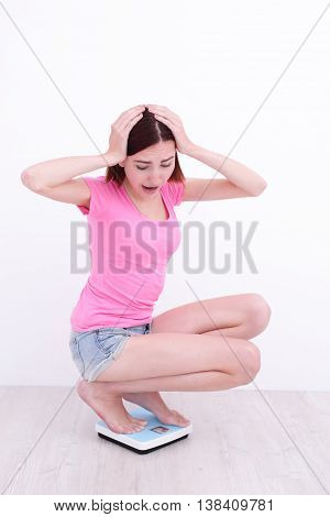 white girl squatting on a scale with her hands on head