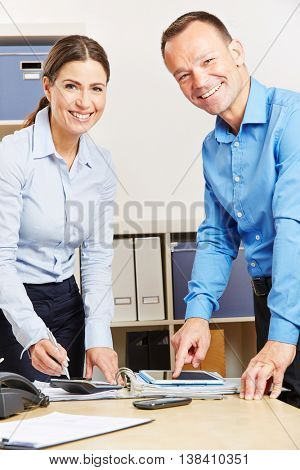 Two business people working with tablet computer and calculator in an office