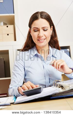 Business woman inf office analyzing files with a calculator at her desk
