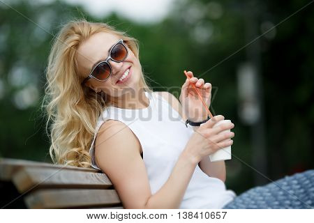 Blonde woman with milkshake wearing sunglasses in park. Image with tilt-shift effect
