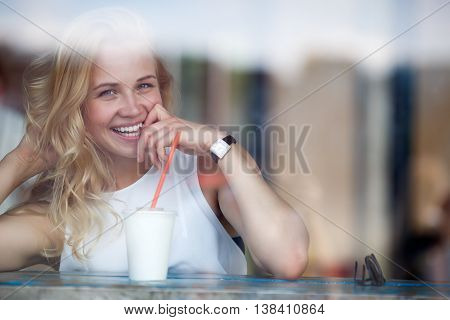 Beautiful blond woman having fun drinking milkshake in caffee