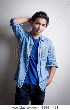 handsome man wear denim shirt and look serious isolated white background asian