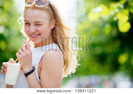 Portrait of cute winking blond woman with milkshake outdoors