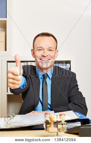 Happy businessman in office holding his thumbs up at his desk
