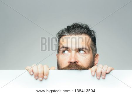 young man with scared face with long hair behind white paper sheet in studio on grey background copy space