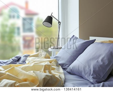 Unmade bed with crumpled blue bed linens
