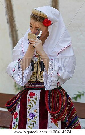 ROMANIA TIMISOARA - JULY 10 2016:Young girl from Serbia in traditional costume make makeup at the international folk festival